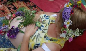 Flower garlands on bump and hair of mother-to-be
